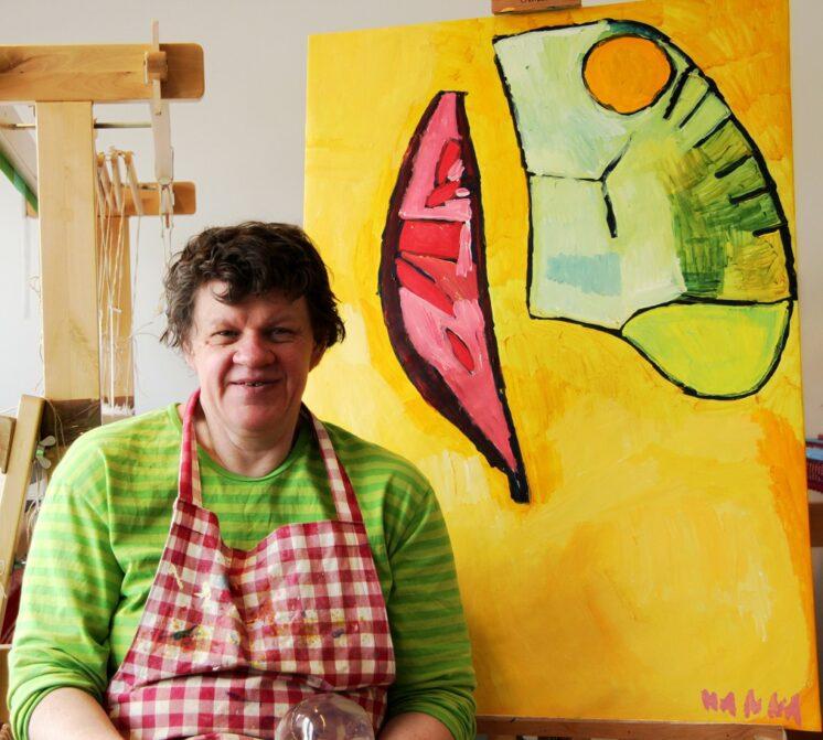 Hanna Keynäs keltaisen Keppuli-maalauksensa vierellä.