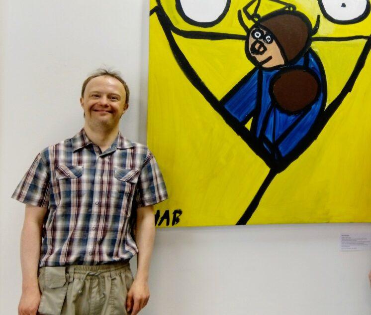 Harri Blomberg keltaisen maalauksensa vierellä