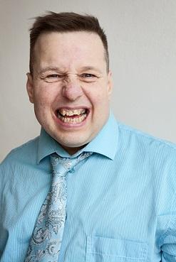 Kettukin vuoden taiteilija Pasi Soukkala hymyilee iloisesti turkoosissa paidassa.
