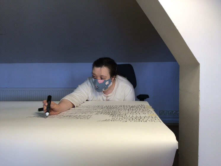 Linnea Mettälä tekstaamassa isolle valkoiselle paperille